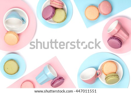creative still life with french dessert macaroons over white background with copy space. food frame top view