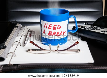 "Creative stress and vacation concept. A blue mug with a message ""Need a break"" standing on a desk with business accessories. - stock photo"