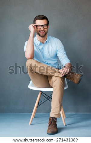 Creative style. Full length of handsome young man adjusting his eyewear and smiling at camera while sitting against grey background  - stock photo
