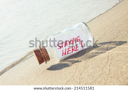 "Creative summer vacation concept. Bottle with a message ""staying here"" on sandy beach"