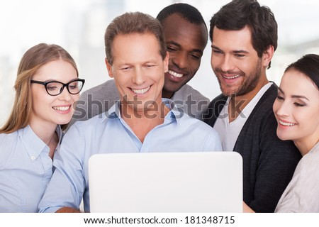 Creative team at work. Group of business people in casual wear standing close to each other and looking at the laptop - stock photo