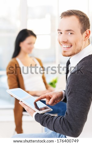 Creative team. Cheerful young man in glasses using digital tablet and smiling while his colleagues working on the background