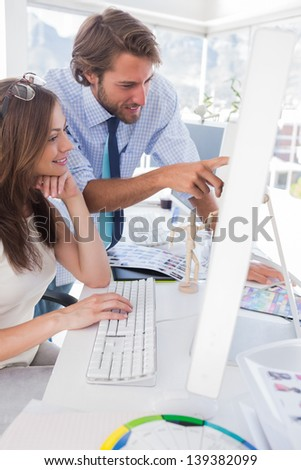 Creative team looking at computer at their desk in modern office - stock photo
