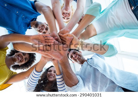 Creative team putting their hands together in circle - stock photo
