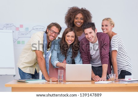 Creative team standing at desk with laptop and smiling at camera - stock photo