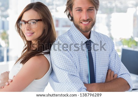 Creative team standing back to back and smiling at camera - stock photo