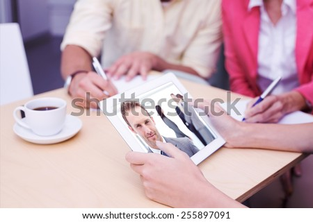 Creative team using tablet pc against proud manager posing in front of his team