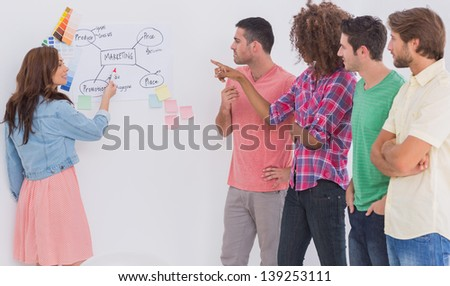 Creative team watching colleague present  flowchart on whiteboard in office - stock photo