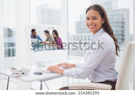 Creative team working together against smiling businesswoman working at her desk - stock photo