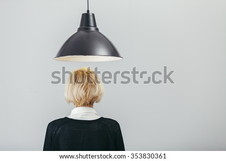 creative thinking concept with a lamp and back head of blond lady - stock photo