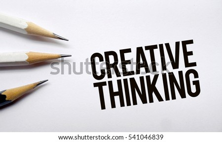 Creative thinking memo written on a white background with pencils