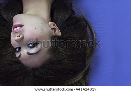 Creative, unusual portrait of a girl on blue background