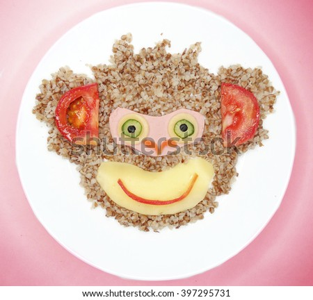 creative vegetable food meal with porridge and sausage monkey form - stock photo