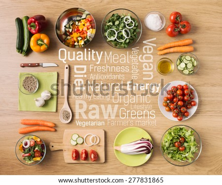 Creative vegetarian cooking at home with fresh healthy vegetables chopped, kitchen utensils and healthy eating text concepts at center - stock photo