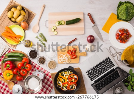Creative vegetarian kitchen with cooking utensils, fresh vegetables and laptop on a wooden table, top view - stock photo