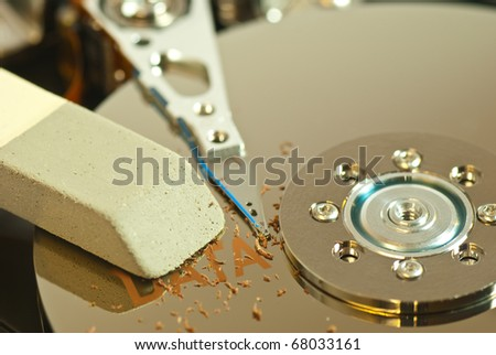 creative view of hard disk internals with eraser symbolizing the erasure of data - stock photo