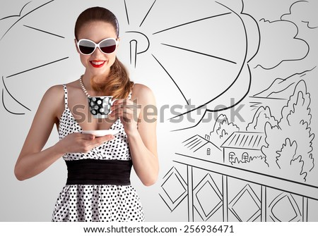 Creative vintage photo of a beautiful pin-up girl under a sunshade drinking tea on sketchy landscape background. - stock photo