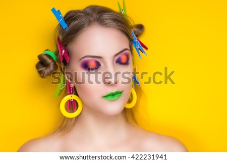 Creative woman lady girl model play with blue pink yellow green colors. Bright conceptual art make-up glows light party time. Multicolored pins, clamps, clips on blond hair. Positive good lifestyle - stock photo