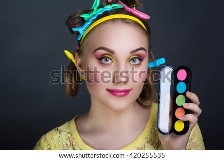 Creative woman lady girl model play with blue pink yellow orange colors. Bright conceptual art make-up glows light party time. Multicolored pins, clamps, clips on blond hair. Holding makeup palette - stock photo