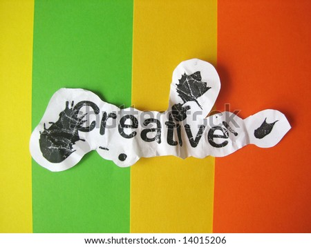 Creative word cut from paper on striped colored background