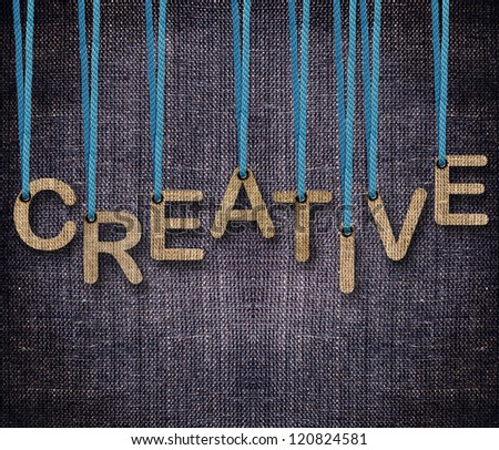 Creative word hanging by rope as puppeteer on sackcloth background. - stock photo