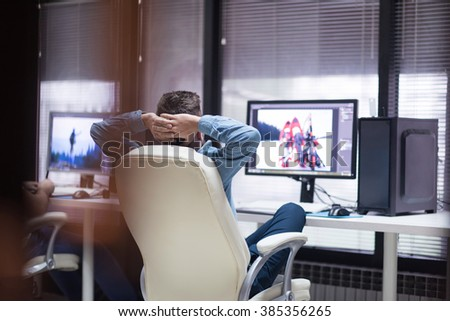 creative worker, photo editor working on graphic tablet at his desktop computer at small startup office - stock photo