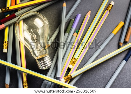 Creative writing, light bulb with many pencils on the table - stock photo