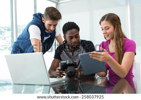 Creative young business team looking at digital tablet at office desk - stock photo