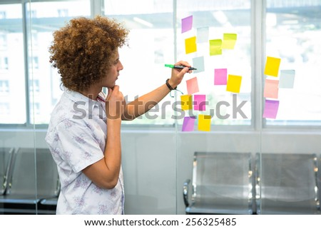 Creative young businessman writing on adhesive note in office