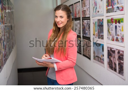 Creative young casual businesswoman writing notes in office