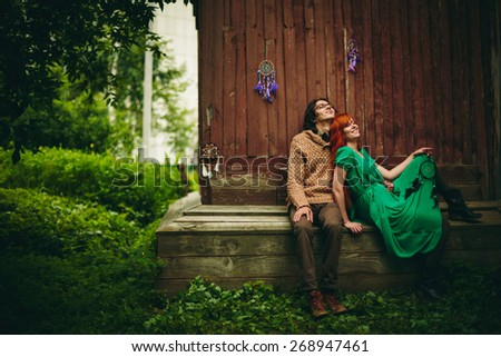 Creative Young Couple in Summer Countryside having fun. Man and Woman sitting near old wooden Wall. Vintage Clothing. - stock photo