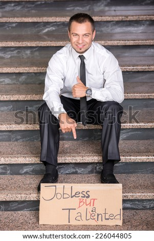 Creative young man is sitting on the stairs with a sign. He is looking for a job. - stock photo