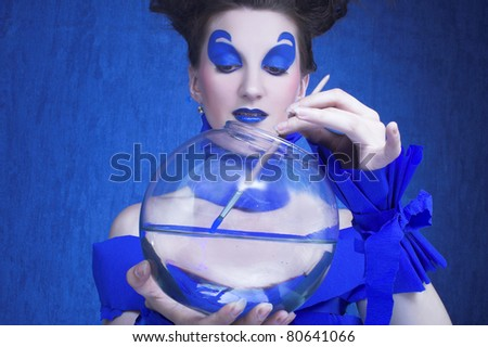 Creative young woman in  blue with sphere aquarium and brush in her hands