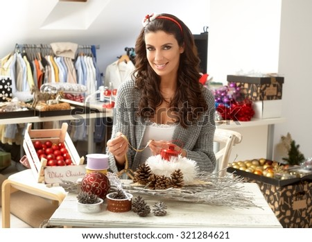 Creative young woman making christmas ornaments centrepiece, smiling, looking at camera. - stock photo