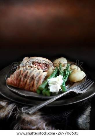 Creatively lit and focused Salmon en Croute with asparagus and new potatoes against a rustic background with copy space. The perfect image for your restaurant lunch menu design. - stock photo