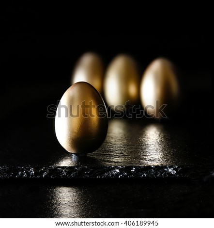 Creatively lit and positioned golden eggs against a black background on oiled slate. Concept image for investments, savings and pensions. Generous accommodation for copy space. - stock photo