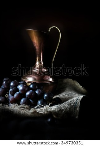 Creatively lit antique jug with black grapes against a dark rustic background with selective focus. The perfect cover image for your wine menu design.  Copy space. - stock photo
