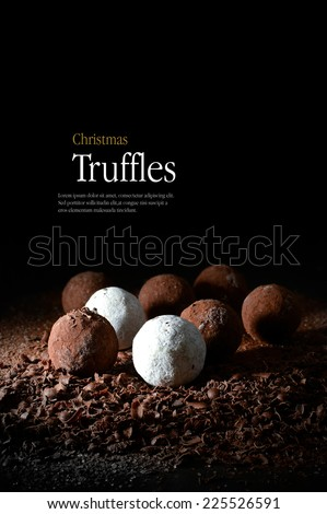 Creatively lit Christmas truffles on a bed of dark chocolate shards against a dark background. Copy space. - stock photo