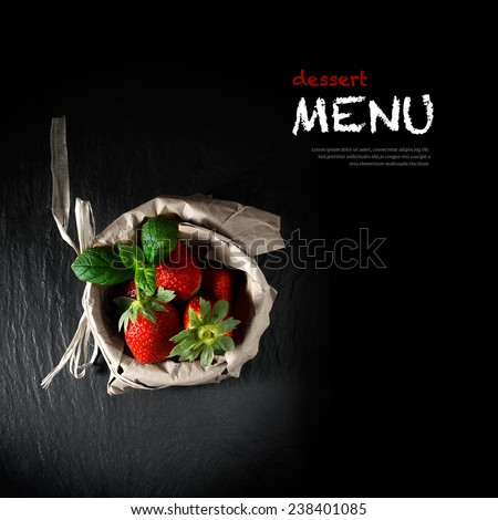 Creatively lit concept image for a dessert menu blackboard. Fresh strawberries and mint leaves in a brown paper bag. Copy space. - stock photo
