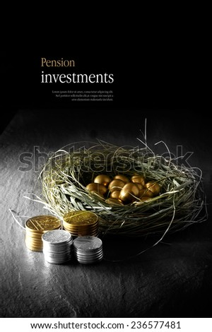 Creatively lit concept image for pension investments. Gold eggs in a grass birds nest with stacked coins against a black background. Copy space. - stock photo