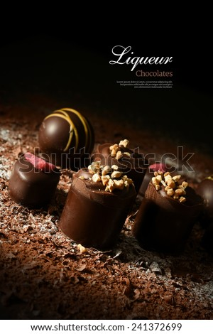 Creatively lit dark liqueur chocolates against a dark background. Copy space. - stock photo