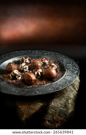 Creatively lit dark liqueur chocolates against a dark rustic background with copy space. Concept image for a restaurant dessert menu cover design. - stock photo
