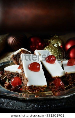 Creatively lit festive iced fruit cake slices with glace cherries, sultanas, currants and raisins soaked in French brandy with thick white fondant icing. Accommodation for copy space. - stock photo