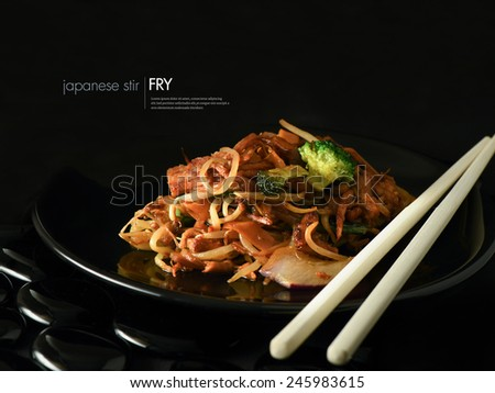 Creatively lit Japanese stir fry against a black background. Copy space. - stock photo