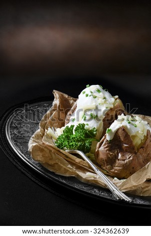Creatively lit meal setting of two baked jacket potatoes with grated cheddar cheese, soured cream and chives in a rustic environment with generous accommodation for copy space. - stock photo