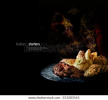 Creatively lit platter of traditional Indian cuisine starters and appetizers against a sparkling Indian background with accommodation for copy space. - stock photo