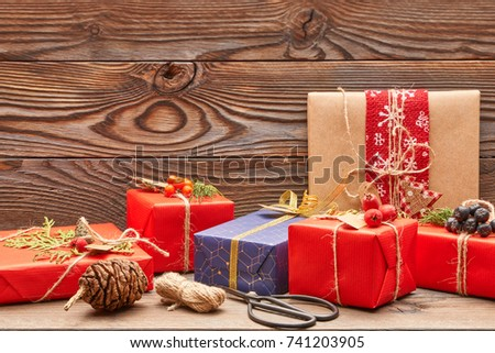 Creatively wrapped and decorated christmas presents in boxes on wooden background. Copy space.
