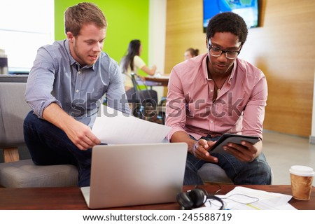 Creatives Having Informal Meeting On Sofas In Design Studio - stock photo