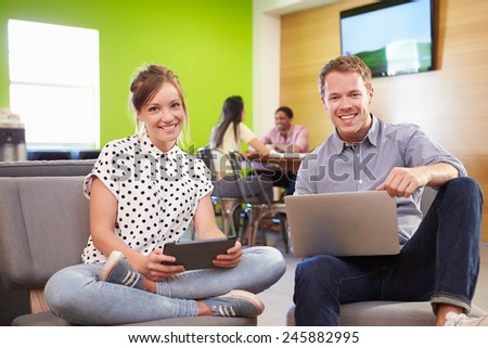 Creatives Having Informal Meeting On Sofas In Design Studio - stock photo