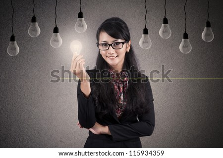 Creativity concept: Beautiful Asian Businesswoman with glasses holds a bright light bulb - stock photo